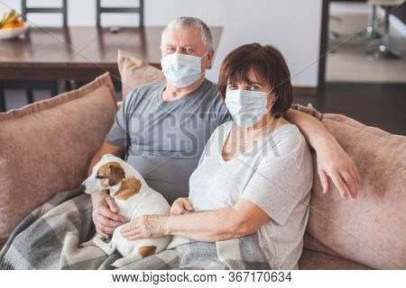 Elderly couple in medical masks during the pandemic Coronavirus CoVid-19. Couple old aged senior people at home with seasonal winter cold illness disease sit down on the sofa.