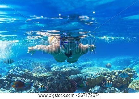 Young woman snorkels in tropical water of Thailand