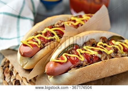 Barbecue Grilled Hot Dog with Yellow Mustard and ketchup on wooden table