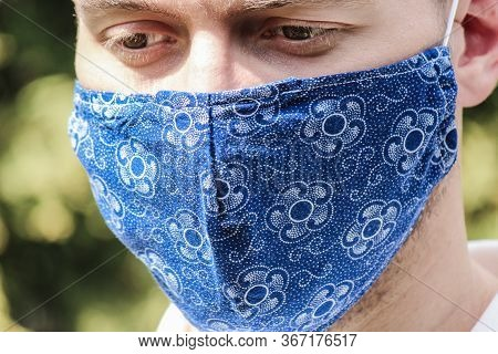 Young Bearded White Man With A Blue Fabric Face Mask During Coronavirus Pandemic. Coronavirus, Covid