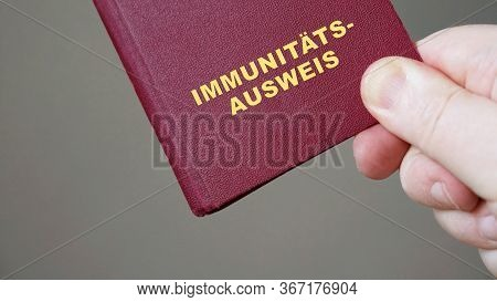 Immunitätsausweis - German Immunity Pass Or Passport - Close-up Hand Holding Mock-up Immune Certific