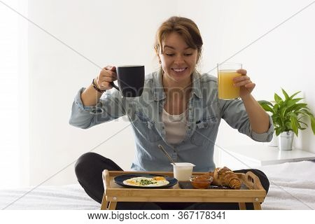 Happy Excited Girl Having Breakfast Holding A Coffee Or Tea Cup And Glass Of A Juice Sitting On The