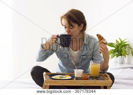 Happy Girl Having Breakfast Holding A Coffee Or Tea Cup And Croissant Sitting On The Bed And Looking