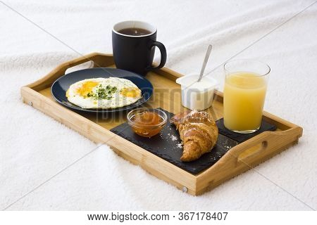Wooden Coffee Tray With Fried Eggs, Croissant With Jam, Cup Of Tea, Juice And Yogurt On White Beddin