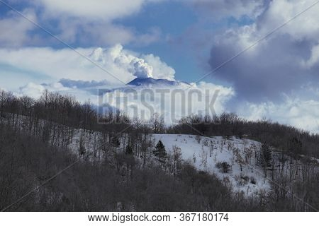 natural landscape of Sicily with snow covered Etna Volcano emit smoke framed by low clouds