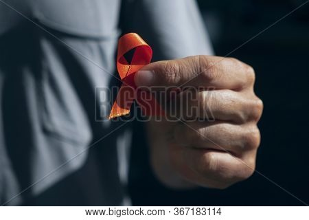 closeup of a young caucasian man with an orange ribbon in his hand, in support of people affected by multiple sclerosis