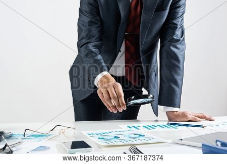 Businessman Analyzing Financial Documents With Magnifying Glass In Hand. Financial Expertise And Con
