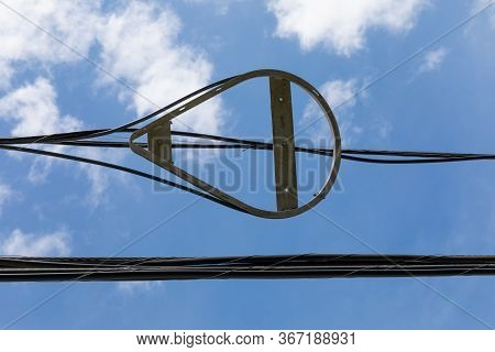 Snowshoe Fiber Optic Radius Limiter Alongside Overhead Power Lines Against Blue Sky With Clouds, Hor