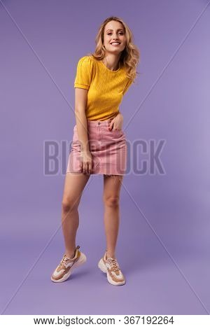 Full length image of nice pleased woman smiling and looking at camera isolated over purple background