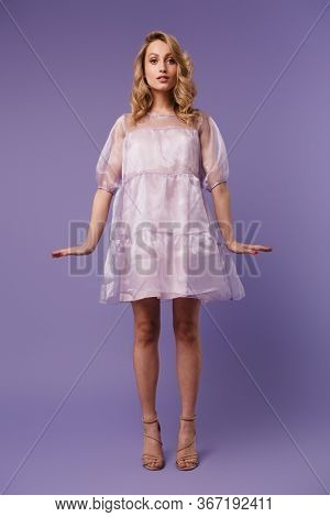 Full length photo of nice caucasian woman posing and looking at camera isolated over purple background