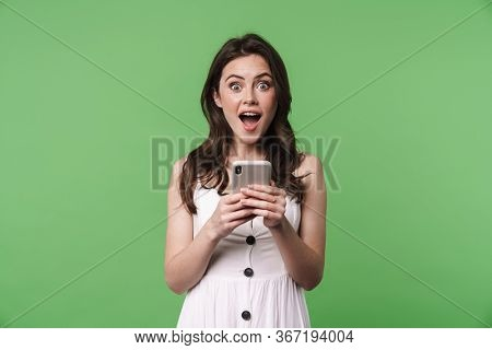 Portrait of a beautiful excited young brunette girl with long hair wearing summer dress standing isolated over green background, holding mobile phone