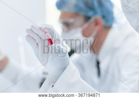 Close Up. Virologist Holds An Ampoule With A New Vaccine.