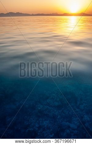 Stunning Seascape On Coral Under Clear Water. Sunset With A Reflection In The Water Taken With Slow