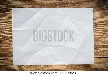 Flat Lay Wooden Table With Paper Sheet. Blank White A4 Format Paper. Space For Writing And Notificat