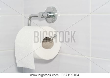Close-up Of A White Roll Of Soft Toilet Paper Neatly Hanging On A Modern Chrome Holder On A Light Ba