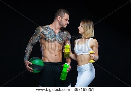Fitness Couple - Woman And Tattooed Muscular Man Posing With Water Bottles And Sport Equipment Over