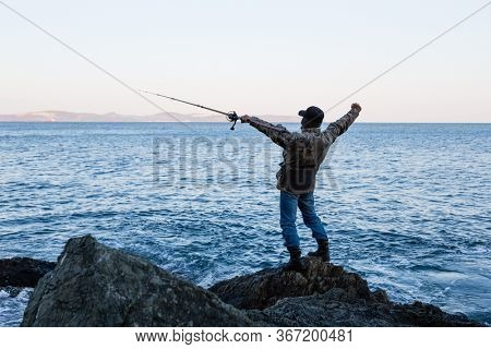 Fisherman meditates before fishing on the rocks by the sea