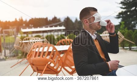 funny man sitting separated in restaurant drinking coffee wearing wrong way medical protective face  mask to protect infection from coronavirus covid-19, social distancing concept