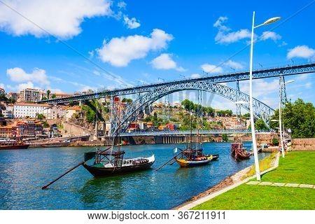 Traditional Boats With Porto Wine Barrels At Douro River And Dom Luis I Bridge In Porto City, Portug