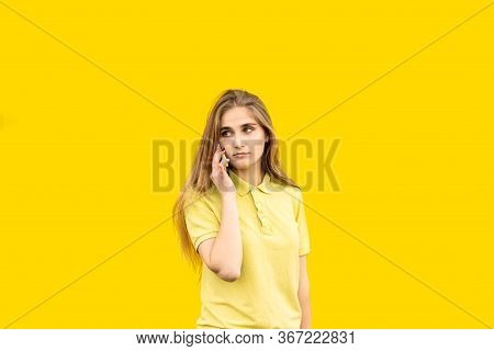 Young Frustrated Young Woman Speaking On The Phone. Grieved By What Was Said. Dressed In A Yellow T-