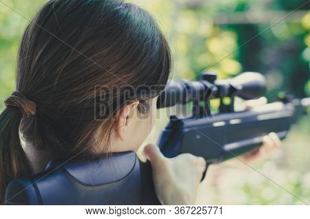 A Girl Looks Into The Scope Of A Sniper Rifle. Back View. Weapons In The Hands Of A Girl. Hunting. W