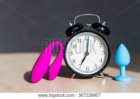 Set Of Sex Toys And An Alarm Clock On The Table. A Concept Of Time For Carnal Joys. Blue Silicone An