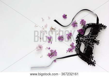 Carnival Black Mask On A White Background. A Composition Of A Carnival Mask And Randomly Scattered S