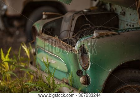 An Old Rusty Green Car. Without Headlights And Hood