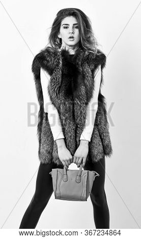 Fashion And Shopping Concept. Female Fashion Model Hold Purse. Woman In Fur Coat With Handbag On Whi