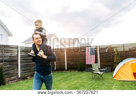Camping In The Backyard. A Dad And Son Set Up A Tent On A Lawn And They Are Spending Time Funny Toge