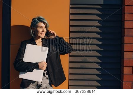 Lovely Woman With Blue Hair Walking In The Street With A Laptop While Talking On Phone And Looking A