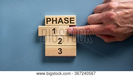 Wooden Blocks Form The Words 'phase, 1, 2, 3,' On Blue Background. Male Hand. Beautiful Background.