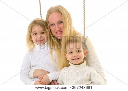 Happy Family Of Mother And Two Kids Sitting Together On Rope Swing, Smiling Mom Hugging Her Son And
