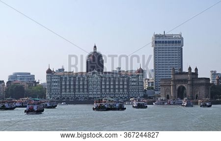 MUMBAI, INDIA - FEBRUARY 15, 2020: Taj Mahal hotel, Gateway of India and tourist boats in water of Arabian Sea on sunset in Mumbai, India