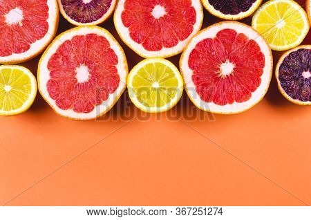 Many Variety Citrus Fruits In A Row Flat Lay In Sunlight On Orange Background. Summer Grapefruit Ora