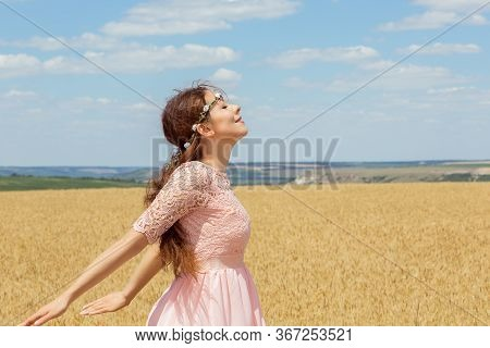 Photo Of Beautiful Woman Standing On Wheat Field, In Golden Rye Land With Open Hands Wants To Fly En