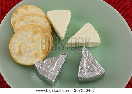 Brie Cheese Mini Slices Unwrapped And Wrapped In Aluminum Foil Packages And Table Water Crackers On