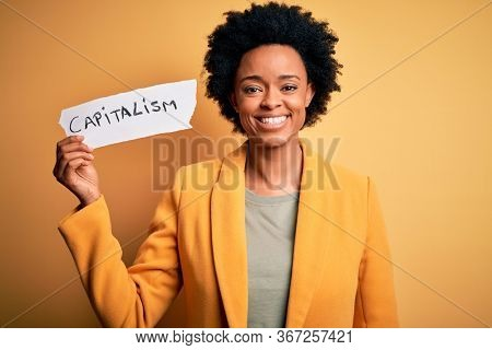 African American afro businesswoman with curly hair holding paper with capitalism message with a happy face standing and smiling with a confident smile showing teeth