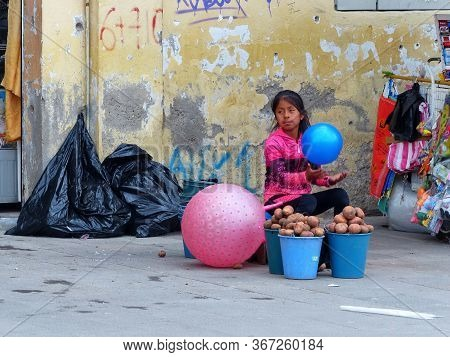Cuenca, Ecuador - December 23, 2018: Girl From Poor Family Sells Potatoes While Playing With Balloon