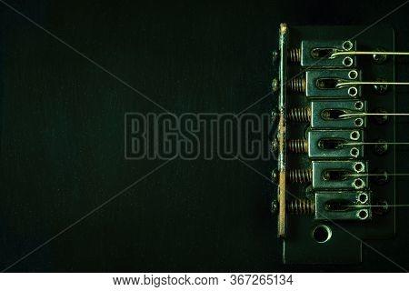 A Closeup Rust Bridge Serves To Fasten Or Tighten The String. Black Vintage Electric Guitar In Dark.