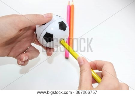 Sharpen Colored Pencils With A Sharpener In The Shape Of A Ball. School Supplies. Selective Shot.
