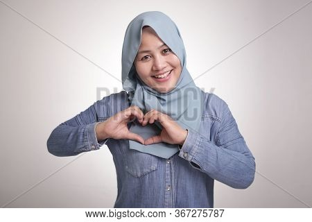 Portrait Of Asian Muslim Woman Smiling At Camera And Making Love Or Heart Sign Gesture With Her Hand