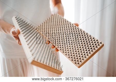Man Holding In Hands Bed Of Nails And Preparing For Morning Yoga Practice. Mindfulness And Alternati