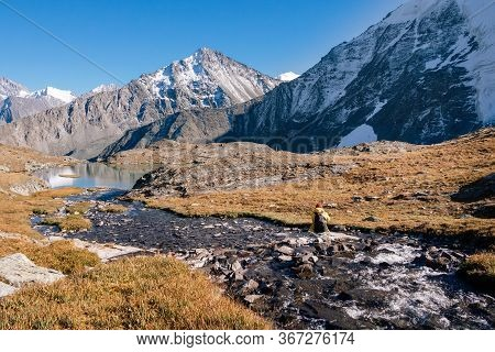 Hipster Young Tourist With Backpack And Camera Sitting On The Bank Of A Mountain River. Altai Mounta