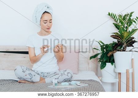 Girl Sitting On The Bed, Making A Manicure Herself And Using A Nail File After A Shower At Home Beca