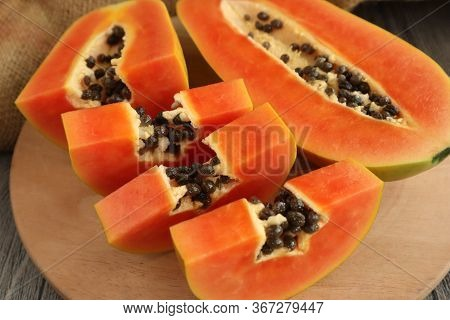 Papaya, Sliced. Delicious Fresh Exotic Healthy Fruits. Close Up Image Of Papaya On Wooden Table