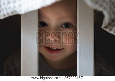 Close-up Portrait Of Smiling Adorable Little Caucasian Boy Playing Behind Crib Fence