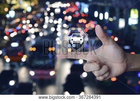 Car With Shield Flat Icon On Finger Over Blur Colorful Night Light Traffic Jam Road With Cars In Cit