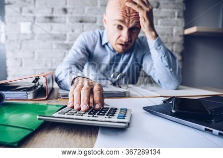 Financial Problems During Crisis. Man Manager With Calculator Counting Money And Bills.