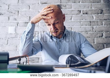 Finacial Problems And Crisis. Stressed Depressed Man Reading Bills And Loan Contract. Finacial Probl